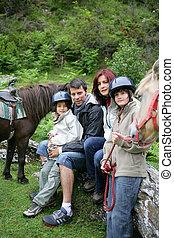Family stood with horses