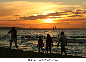 family sunset stroll against, visible port cranes in...