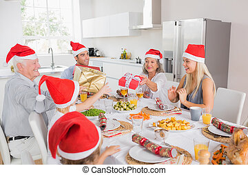 Family swapping christmas presents - Family wearing santa...