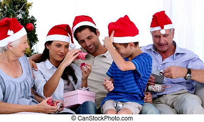 Family swapping gifts at christmas at home on sofa
