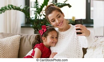 family taking selfie by smartphone at home - christmas,...