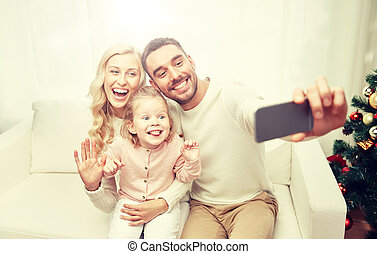 family taking selfie with smartphone at christmas -...