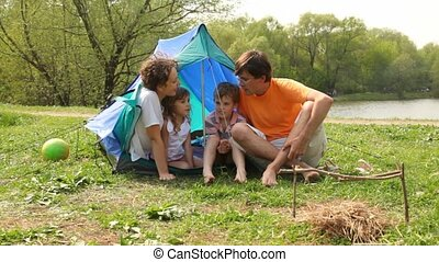 Family talking near tent and ball in park