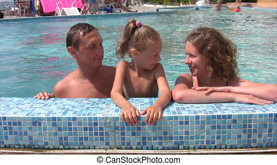 family talks in swimmig pool outdoor