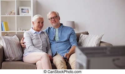 happy senior couple watching tv at home - family, technology...