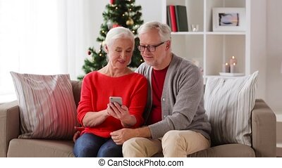 happy senior couple with smartphones at home - family,...