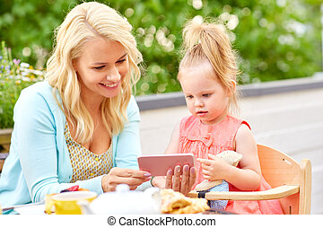 mother and daughter with smartphone at cafe