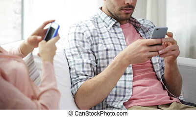 couple with smartphones texting at home - family,...
