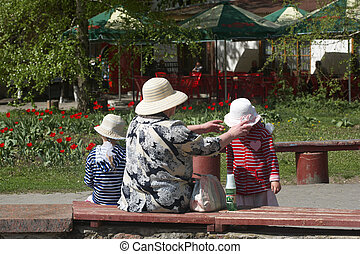 Family - The grandmother with two girls have a rest in park