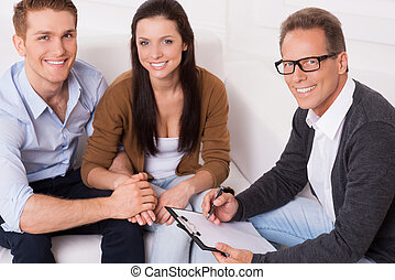 Family therapy . Top view of happy young couple and confident psychiatrist sitting together and smiling