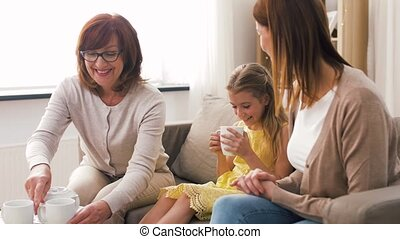 mother, daughter and grandmother having tea party - family,...