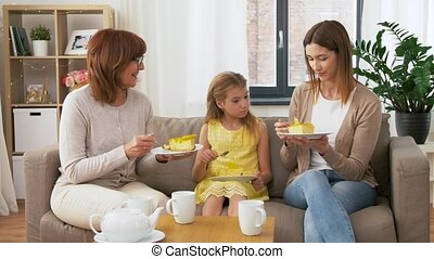 mother, daughter and grandmother eating cake - family, three...