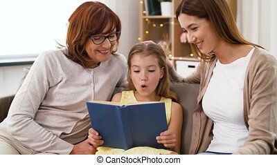 mother, daughter and grandmother reading book - family,...