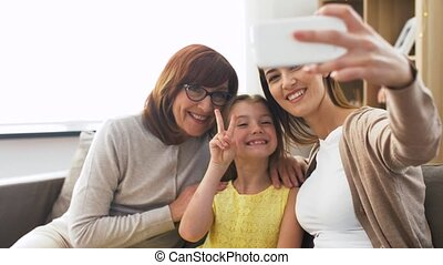 mother, daughter and grandmother taking selfie - family,...