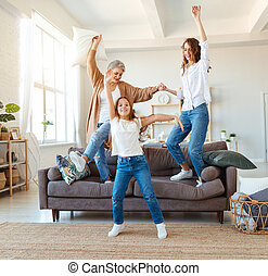 family three generations grandmother, mother and child dancing, jumping and laugh at home
