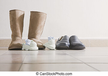 Family - Three pairs of shoes by the front door of a home.