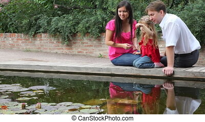 family throw coins into water in park