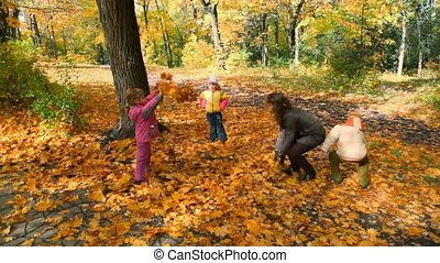 family throwing leaves in park