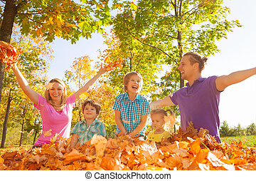 Family throwing leaves in the air during play