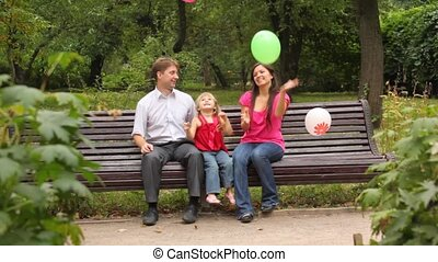 family throws balloons sitting on bench in park