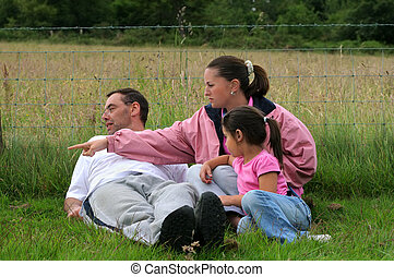 Family Time - Man, woman and little girl sitting down...