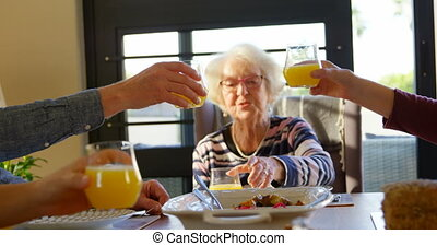 Family toasting glasses of juice on dining table at home 4k...