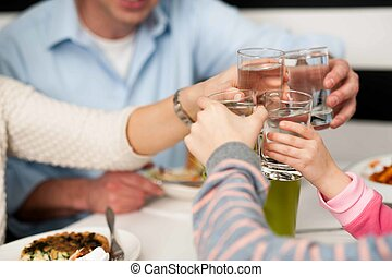 Family toasting water glasses in celebration