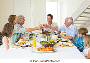 Family toasting while having meal - Happy multigeneration...