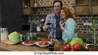 Family Together In Kitchen Before Dinner, Parents Drink Wine Embracing While Children Watch Video On Digital Tablet