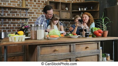 Family Together In Kitchen Father Helping Daughter To Cut Vegetables While Son And Mother Use Cell Smart Phone Talking Parents With Two Kids Preparing Food At Home