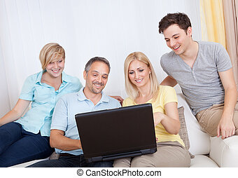 Family together sitting on the couch with laptop
