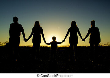 Family Togetherness Silhouetted - a family holding hands in...