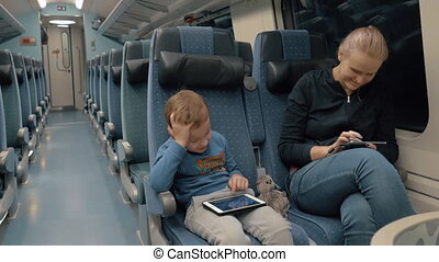 Family traveling by train and entertaining with electronics...
