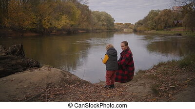 family trip in woodland, mother and little boy are resting ...