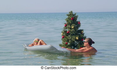 Family tropical beach vacation mother with daughter in water near Christmas tree