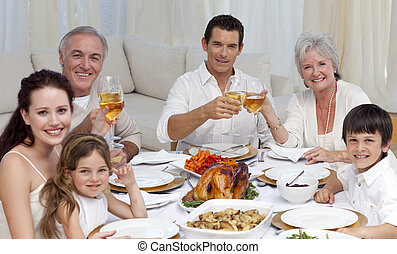 Family tusting with wine in a dinner smiling at the camera