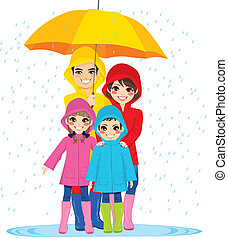 Family Under Umbrella - Happy family with raincoats under...