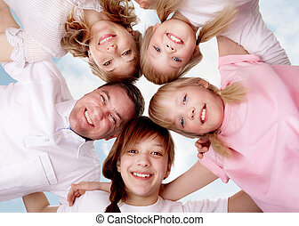 Family union - A young friendly family making circle while...