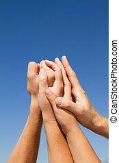 family unity - a familys hands meshed together on a blue...
