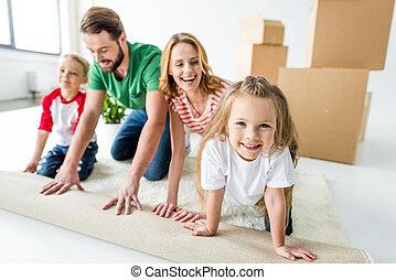 Family unrolling carpet
