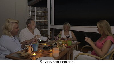 Family using cells and laptop during dinner