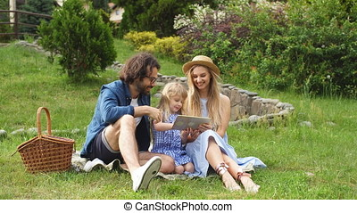 Family using digital tablet during picnic at countryside