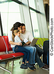 family using laptop at airport