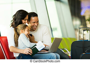 family using laptop computer at airport