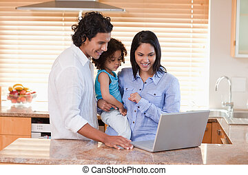 Family using laptop in the kitchen together