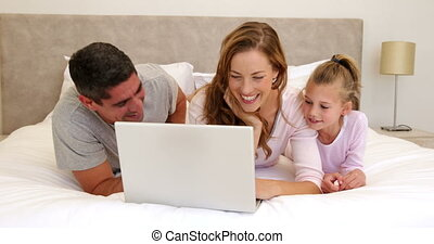 Family using laptop together on bed