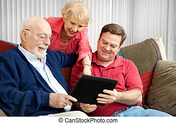 Family Using Tablet PC - Adult son and elderly parents using...