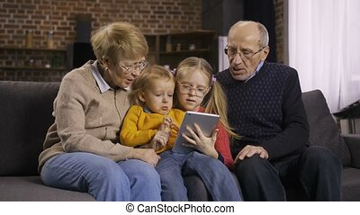 Family using tablet pc on sofa together at home - Two...