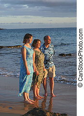 A beautiful, dressed up family with on a beach in maui.