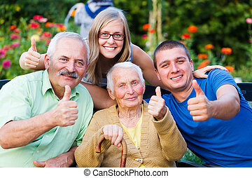 Happy, contented family showing thumbsup for the quality of the residential care of grandmother.